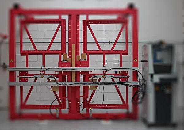 una porta simulata e il banco utilizzato per effettuare i cicli di durabilità del dispositivo antipanico attraverso una gamma completa di operazioni di apertura e chiusura